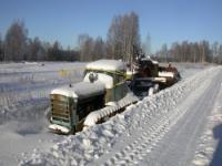 Гусеничный трактор около зимней дороги.